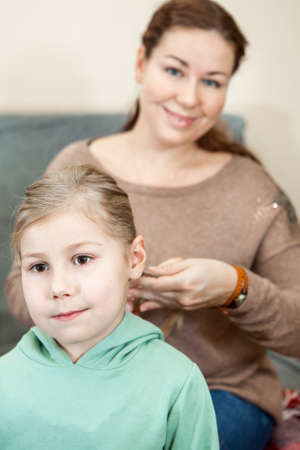 combing: Mother raiding the hair of her child sitting in domestic room