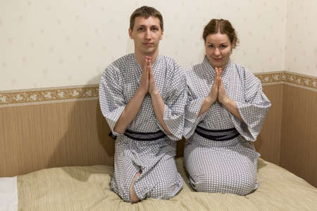 Young Caucasian couple sitting in traditional robes in japanese hotel room, Japan photo