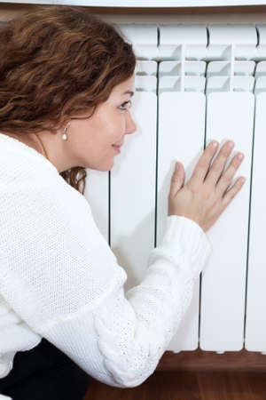 Woman leaning his hand and cheeks to central heating radiator