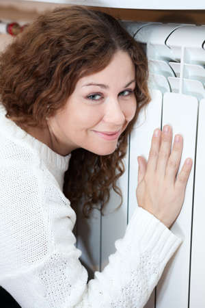 warmness: Attractive woman leaning his to central heating radiator