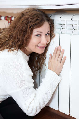 Smiling woman leaning his hand and cheeks to central heating radiator Stock Photo