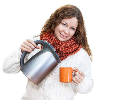 Pretty woman pouring hot water from the kettle into a cup, isolated on white background photo