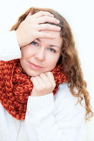Diseased cold woman in a red scarf and sweater, white background photo