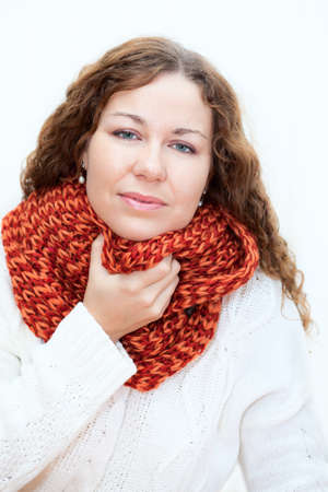 tremble: Young woman in warm clothes with a sore throat, white background Stock Photo