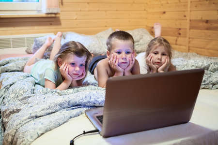 woman lying in bed: Three children looking at laptop monitor before sleeping in bed