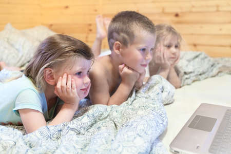 Lovely kids looking at computer monitor while laying in bed photo