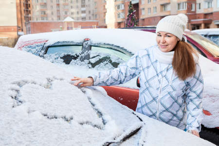 Beauty woman in the winter clothes with heart drawing on windshield of car photo