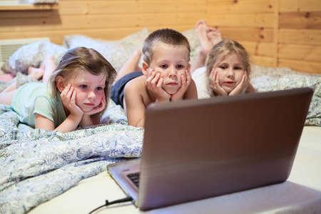 Three children looking at laptop monitor while laying in bed photo