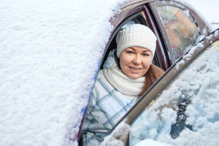 Smiling woman sitting inside of snow covered car photo