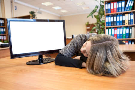 Young office worker sleeping at working place near blank screen photo