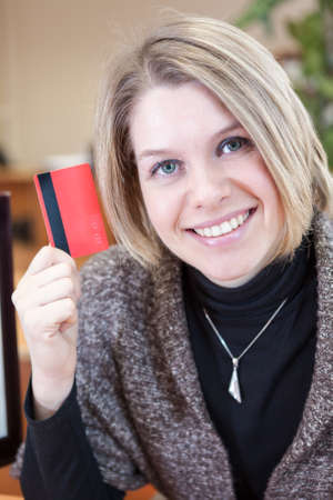Smiling Caucasian woman showing credit card in hand photo