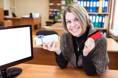 Young woman with credit card and gift in hands sitting near blank screen photo
