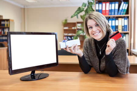 Young woman holding a credit card sitting at her desk in front of screen computer photo