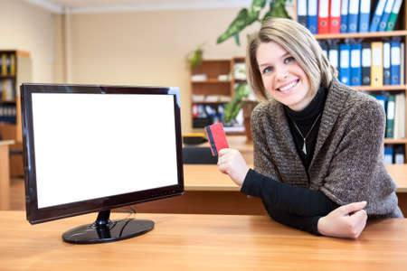 Office worker in front of a computer monitor with a credit card in hand photo