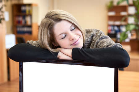 Young woman sleeping over blank screen of monitor in office photo