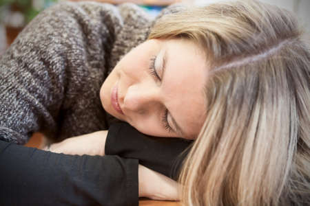 Close up face of attractive woman sleeping on table photo
