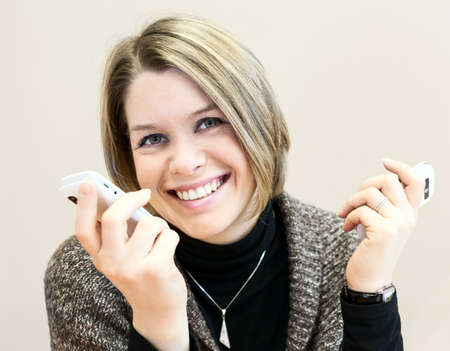 Attractive happy young businesswoman chatting on two smartphones photo