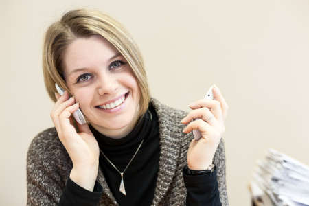 Beauty happy young businesswoman chatting on two smartphones in office photo