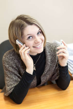 Pretty bland hair woman calling with two mobiles photo