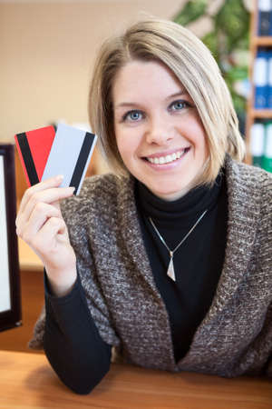 Smiling Caucasian woman holding two credit cards in hand photo