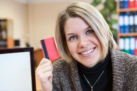 Young happy smiling woman paying by plastic card, at office photo