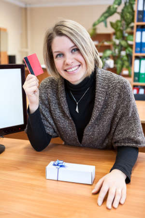 Young blond woman holding a credit credit and smiling with gift on table photo