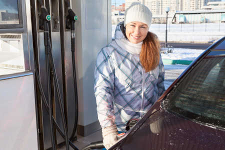 refuel: Woman in winter clothes standing with refuel pistol near car