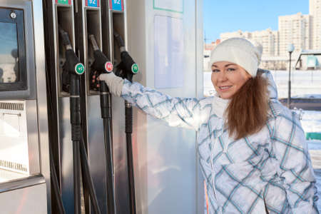 fueling: Young woman holding fueling nozzle at petroleum station at winter Stock Photo