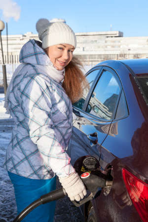 fueling: Cheerful Caucasian woman fueling car at winter season Stock Photo