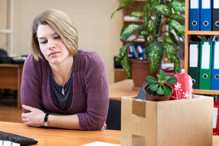 dismissal: Dismissal - frustrated woman at a desk with a box with things