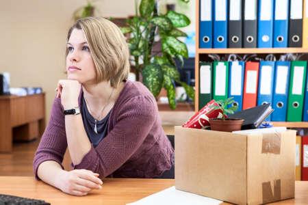 Nadenkende vrouw met verzamelde in doos dingen zitten te wachten