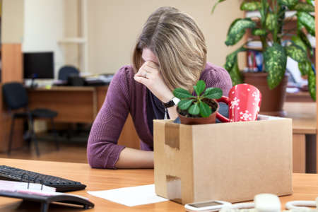 Dismissal at work, weeping employee with things to take away Imagens