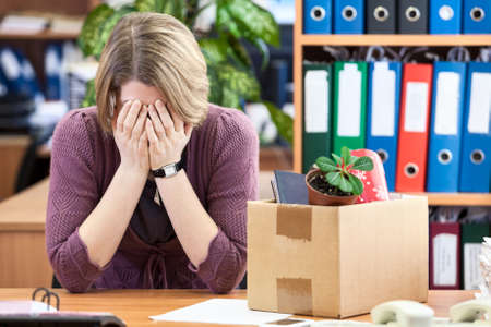 Dismissed woman crying, last time sitting at your desk photo