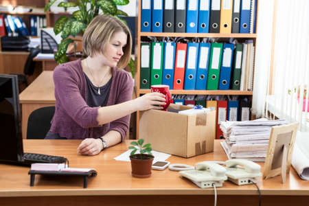 Fired woman collecting things in cardboard box in the workplace
