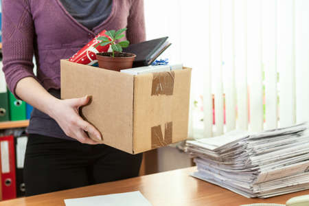 Unrecognizable office employee with collected in box things Imagens
