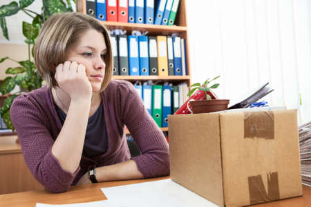 dismissal: Sad woman in the workplace after dismissal