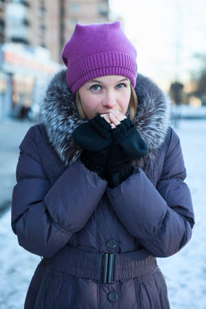 Woman warming hands at the cold winter weather photo