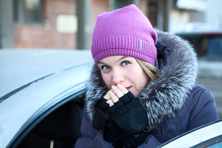 Portrait of young woman warming her hands near the car photo