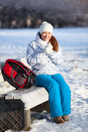 Young woman with backpack resting in winter park photo