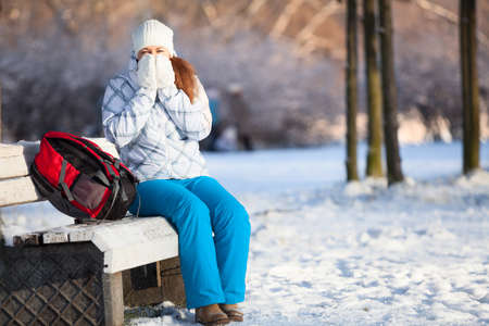Woman with backpack heating hands in mittens at winter, copyspace photo