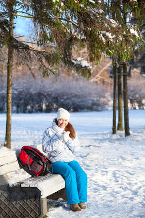 Pretty woman with backpack sitting on a bench in winter park photo