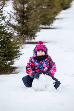 Girl making snowball for a snowman at winter photo
