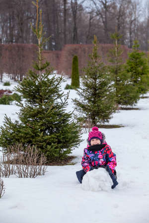 Young girl rolling snowball for a snowman at winter photo