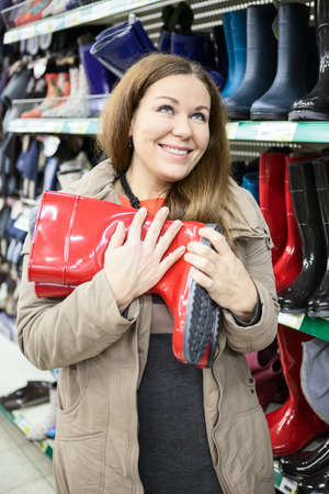 rubber sole: Woman with red waterproof shoes in hands buying in the shop