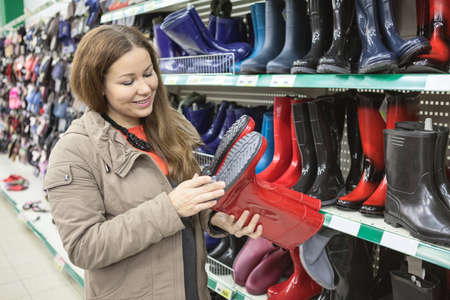 rubber sole: Woman in the store looking for the right size rubber boots Stock Photo
