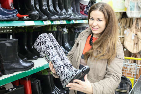 rubber sole: Pretty woman near the shelves with watertights in shop