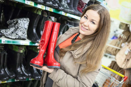 rubber sole: Young woman holding red watertights when buying in shop Stock Photo