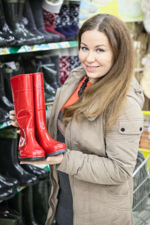 Smiling woman holding red watertights when buying in shop photo