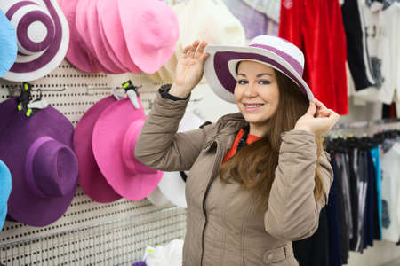 Woman trying summer hat in shop center photo