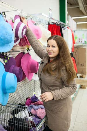 Caucasian woman looking for summer hats on wholesale shop photo